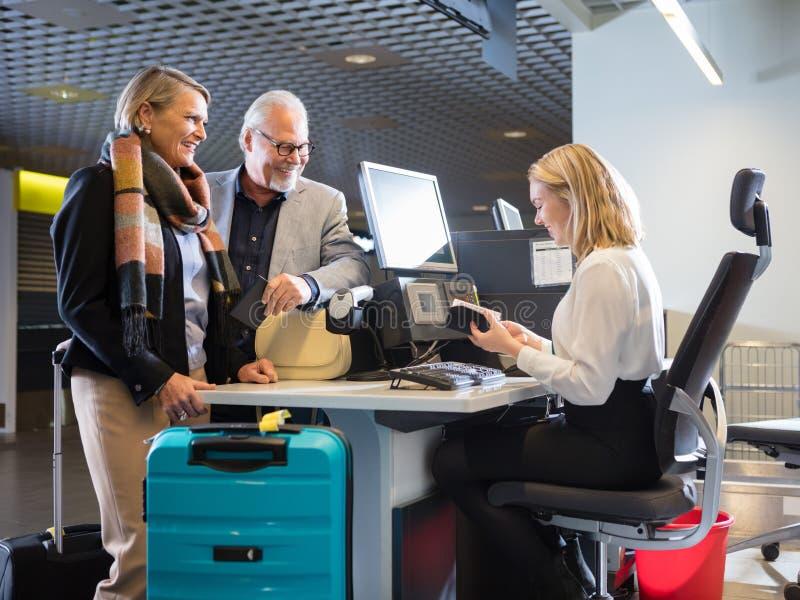 看职员的企业夫妇检查护照在机场Ch 免版税库存照片