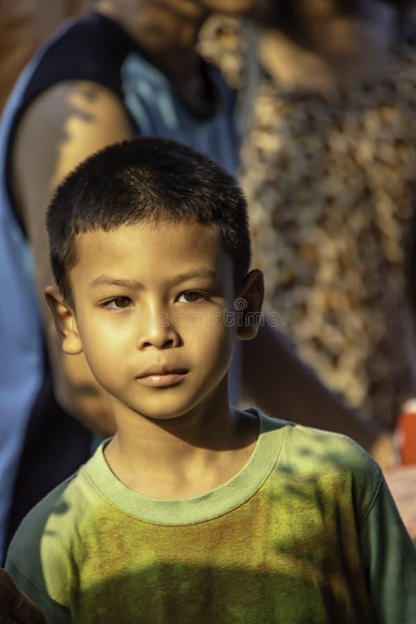 看背景迷离人的画象亚洲男孩身分 免版税库存照片