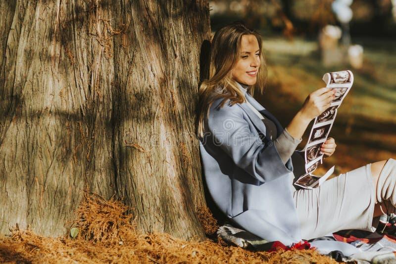 看胎儿超声波图象的年轻人孕妇在公园 库存图片