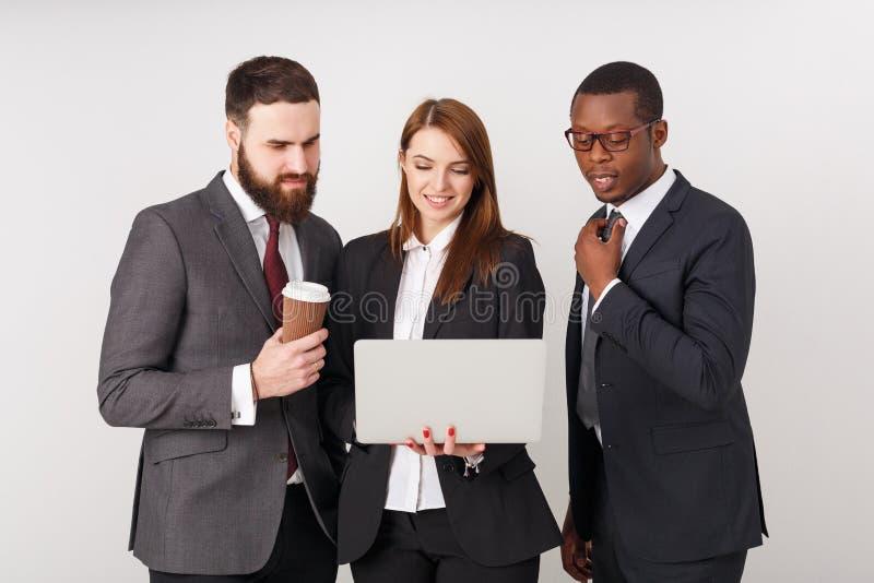 看膝上型计算机和微笑的商人 免版税库存照片
