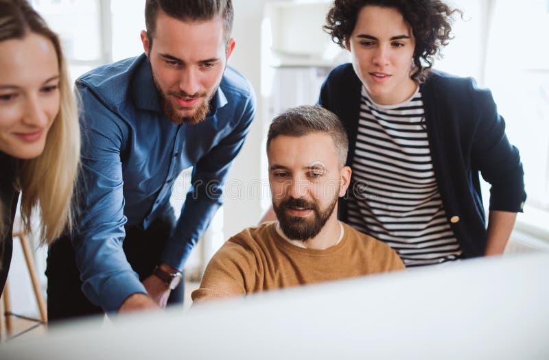 看膝上型计算机屏幕的小组年轻买卖人在办公室,讨论问题 免版税图库摄影