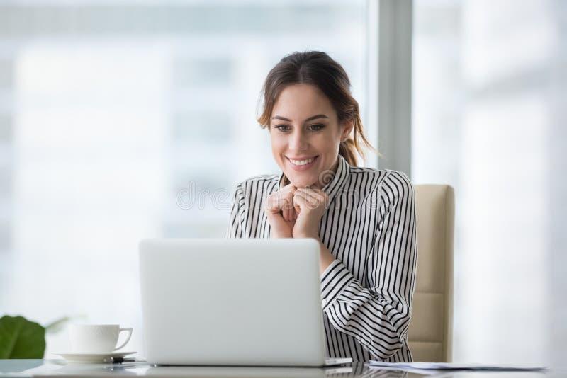 看膝上型计算机屏幕的愉快的微笑的年轻女人 图库摄影