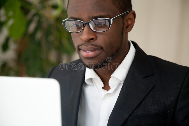 看膝上型计算机屏幕的被聚焦的非裔美国人CEO读ne 免版税库存照片
