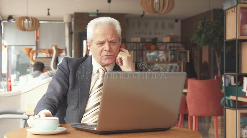看膝上型计算机屏幕的资深商人 免版税库存照片