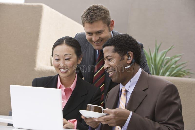 看膝上型计算机的商人在他们的咖啡休息期间 免版税库存图片