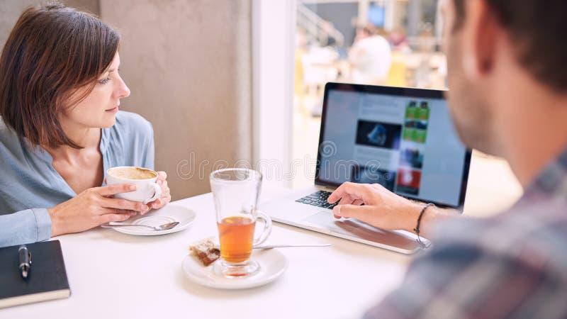 看膝上型计算机的妇女紧的射击供以人员肩膀 免版税库存照片