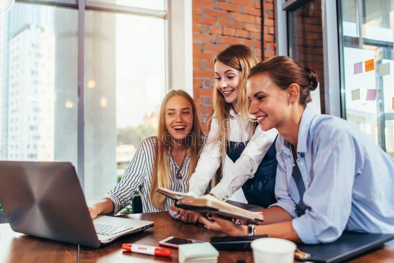 看膝上型计算机的小组学生休假在学习以后在大学研究室 免版税库存照片