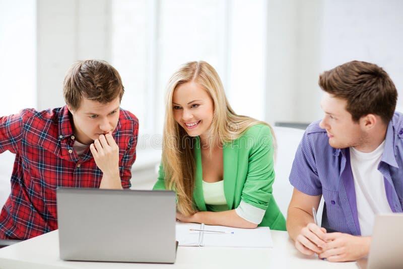 看膝上型计算机的微笑的学生学校 免版税库存照片