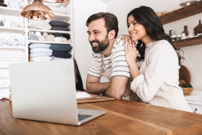看膝上型计算机的快乐的夫妇画象,当在家时烹调酥皮点心在厨房里 免版税库存照片