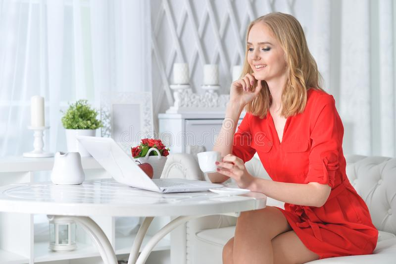 看膝上型计算机的红色礼服的美丽的白肤金发的年轻女人 库存照片