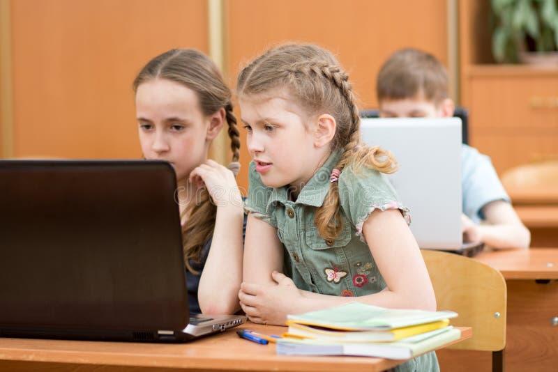 看膝上型计算机的聪明的女小学生和男小学生画象在教室 免版税库存图片