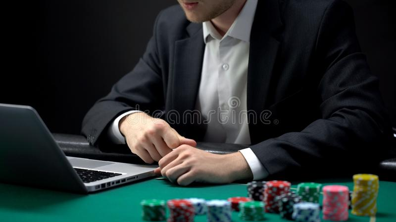 看膝上型计算机网上扑克牌游戏,赌博娱乐场瘾的订婚的年轻赌客 库存图片