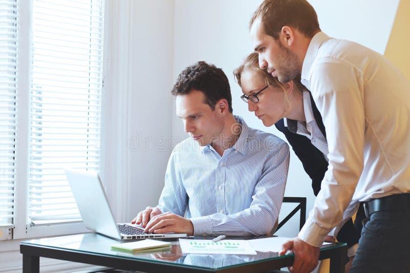 看膝上型计算机,工商管理硕士学生的小组年轻商人 库存图片