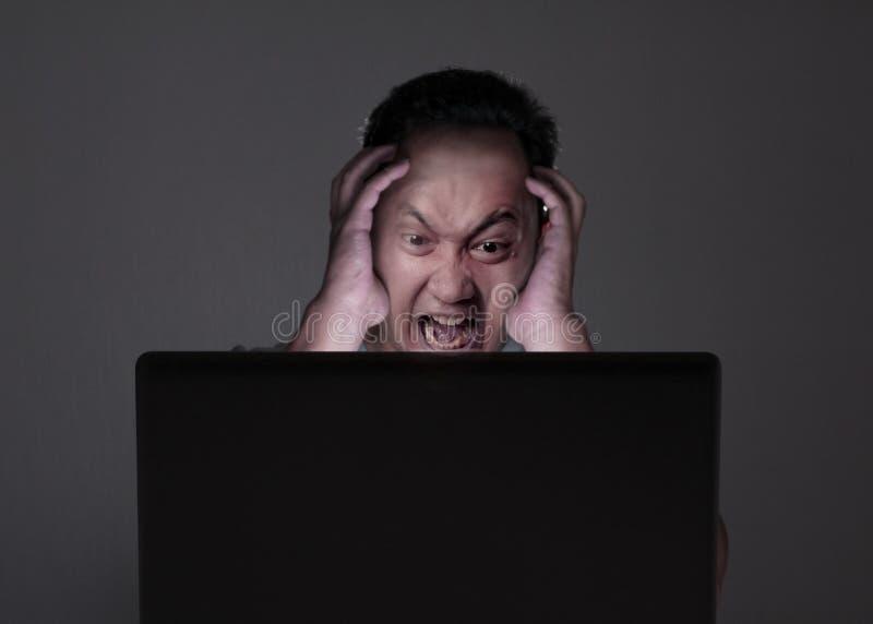 看膝上型计算机,恼怒的姿态的年轻人 免版税库存照片