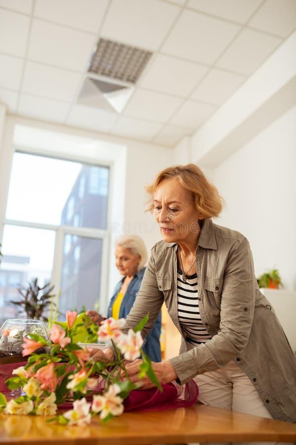 看花束的快乐的年迈的妇女 免版税库存图片