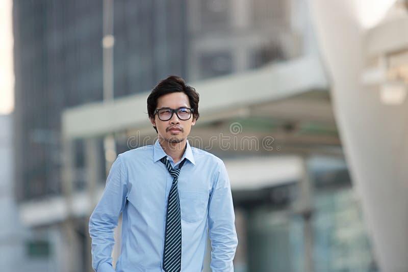 看英俊的年轻亚洲的商人画象站立和批转在被弄脏的都市大厦城市背景 免版税库存图片