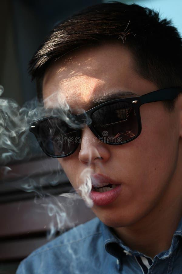 看英俊的年轻亚裔的人向下抽烟和 免版税库存照片