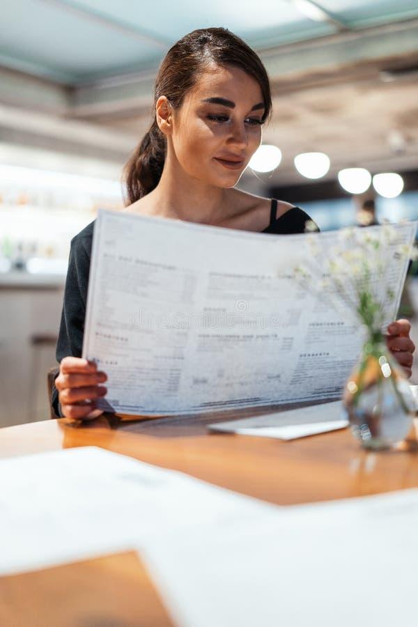 看菜单的年轻美丽的妇女决定什么对在现代咖啡馆的命令 免版税图库摄影