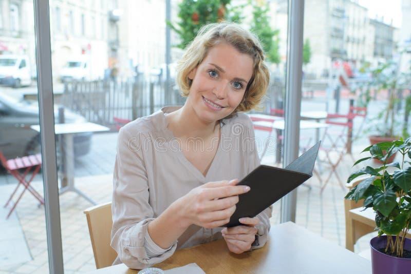 看菜单的美丽的妇女在餐馆 库存图片
