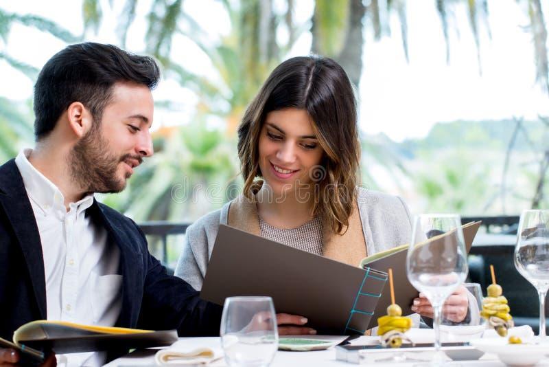 看菜单的年轻夫妇在餐馆 库存图片