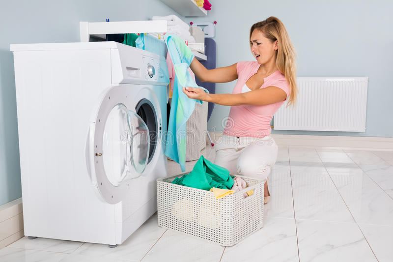 看蓝色T恤杉的妇女在洗涤以后 免版税库存照片