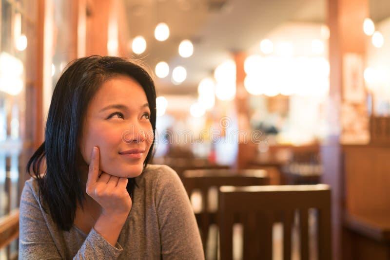 看被晒黑的亚裔的女孩向上认为和复制空间,想知道的菜单为晚餐,餐馆广告概念指令 免版税库存图片