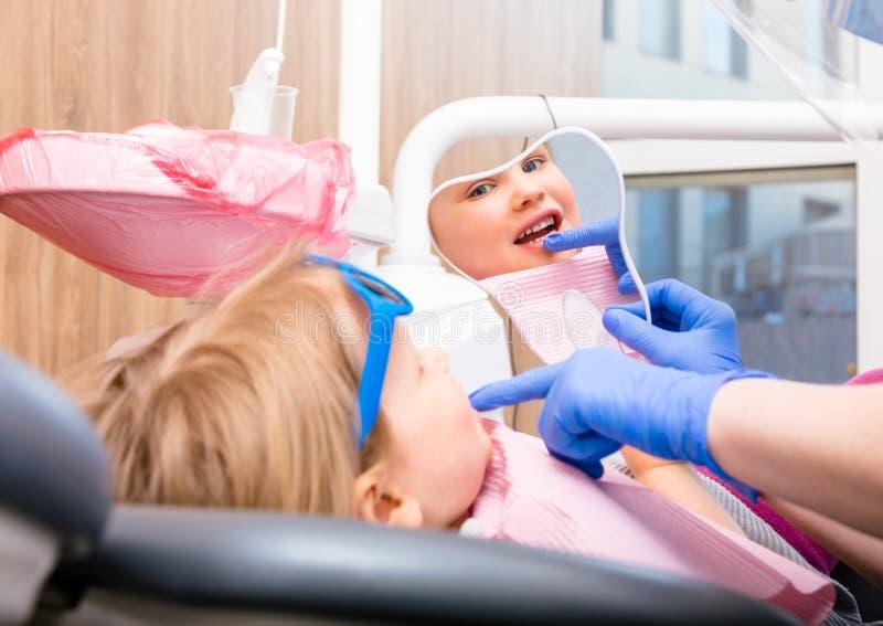 看被治疗的牙的女孩通过在小儿科牙齿诊所的镜子 免版税图库摄影