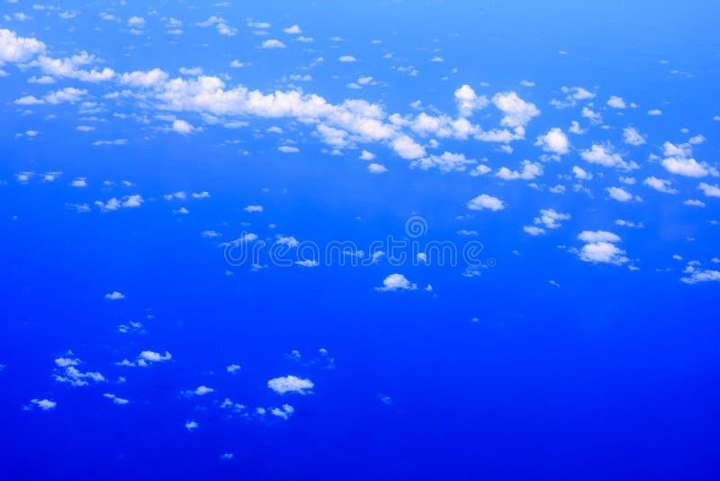 看见天空蔚蓝、白色云彩和深蓝色海的飞机窗口的看法 库存照片