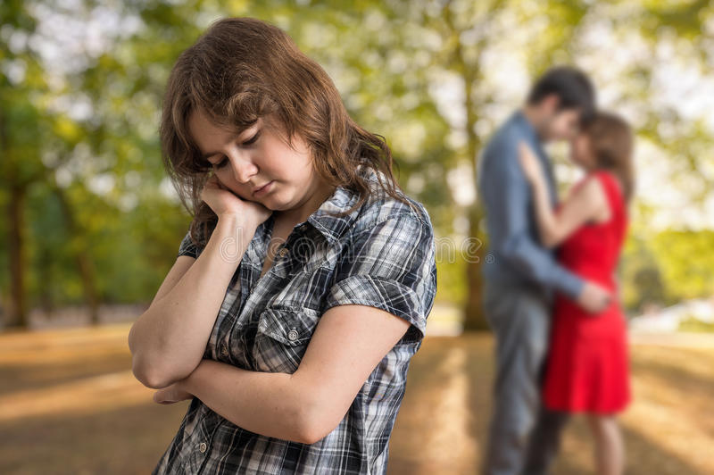 看见她的男朋友的年轻哀伤的嫉妒女孩挥动与另一名妇女 库存图片
