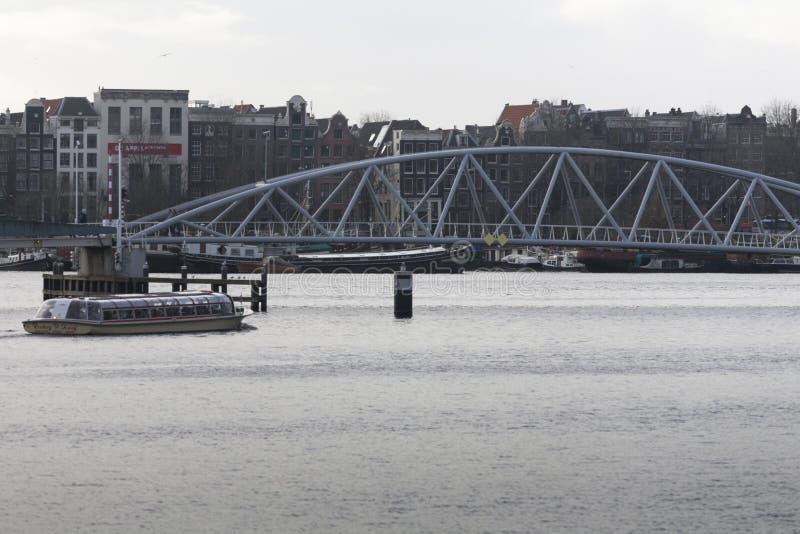 看见小船的站点接近J J van der维尔德桥梁, Prins亨德里克klane是在背景阿姆斯特丹中荷兰 免版税图库摄影