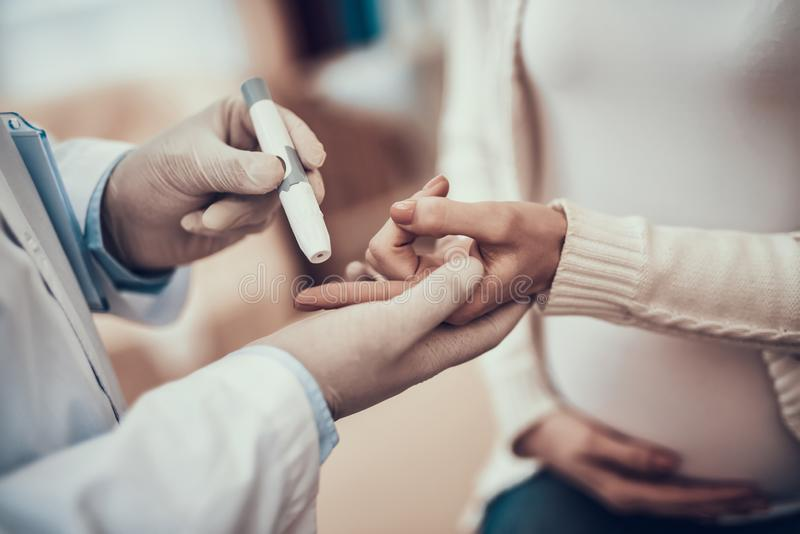 看见患者的印度医生在办公室 医生测量孕妇血糖有女儿的 免版税图库摄影
