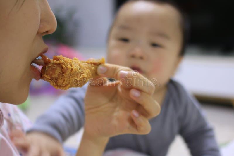 看见母亲的亚裔婴孩吃与一只羡慕眼睛的炸鸡 库存图片