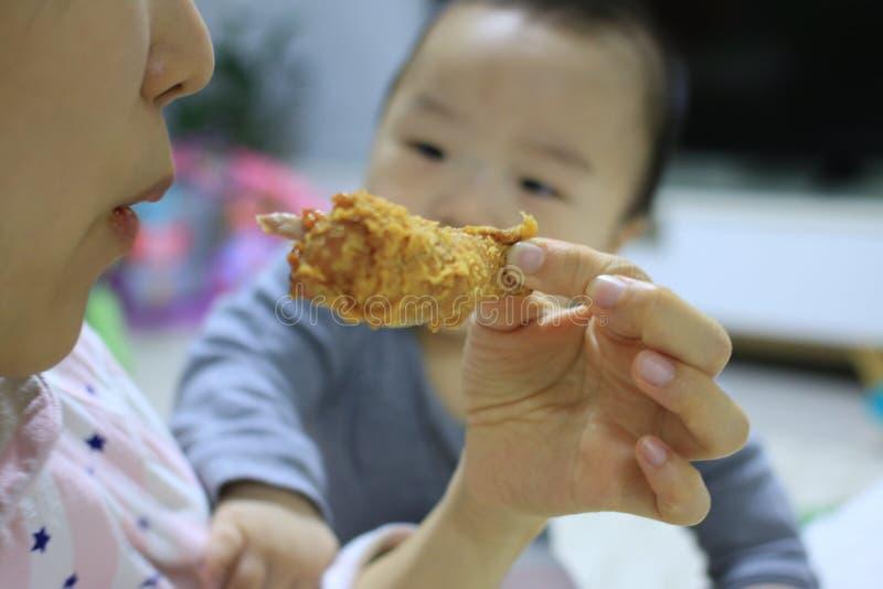 看见母亲的亚裔婴孩吃与一只羡慕眼睛的炸鸡 库存照片