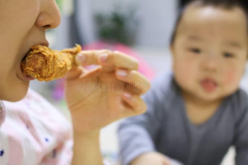 看见母亲的亚裔婴孩吃与一只羡慕眼睛的炸鸡 免版税图库摄影