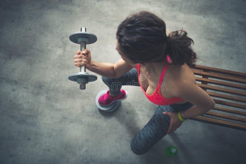 看见从健身妇女举的哑铃上 库存图片