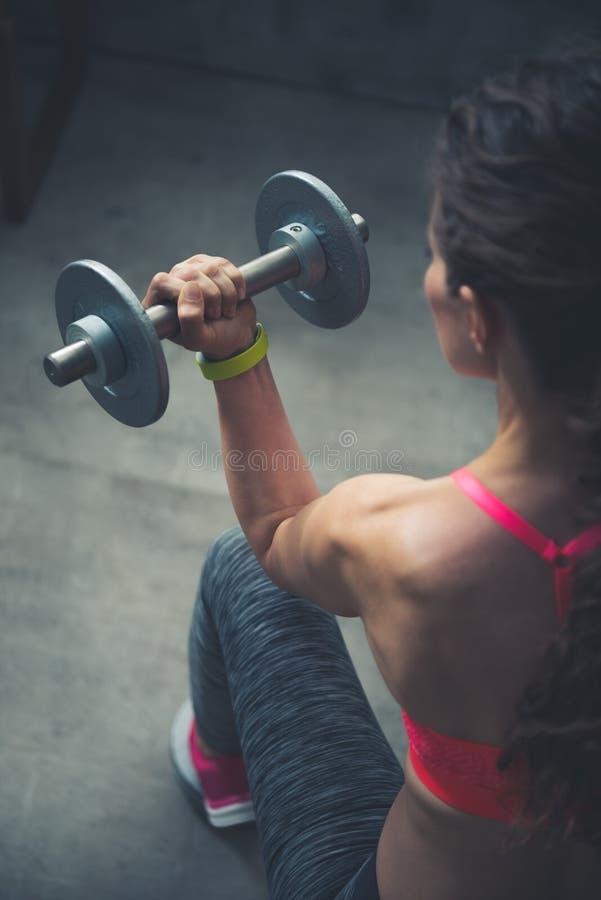 看见从后面健身妇女举的哑铃 免版税库存照片
