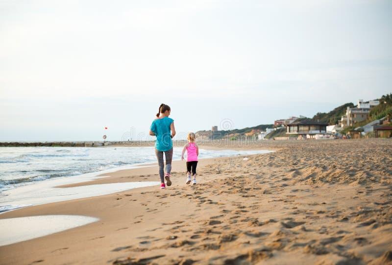 看见从后面,跑在海滩的母亲和女儿 免版税库存图片