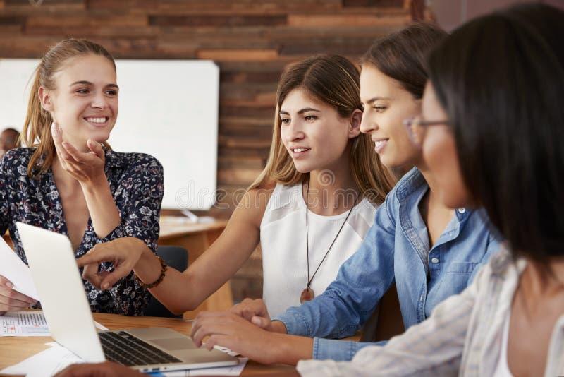 看计算机的四个女性同事在办公室 库存照片