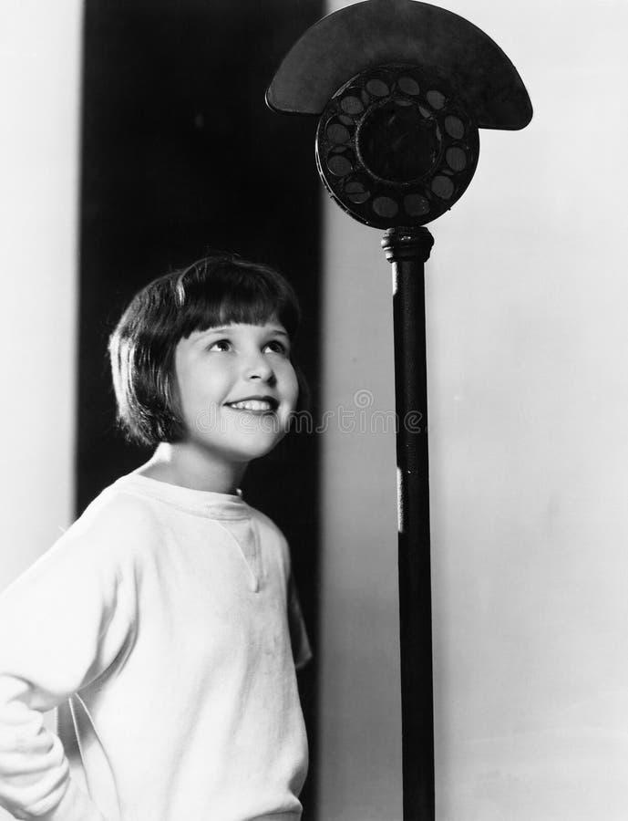 看话筒的一个女孩的档案和微笑(所有人被描述不更长生存,并且庄园不存在 一口 库存图片