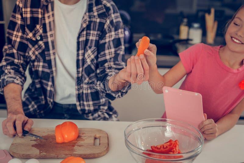 看起来一件桃红色的T恤杉的俏丽的金发女孩满足 库存照片