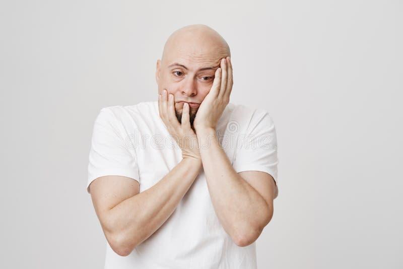 看起来不快乐的疲乏的秃头的人画象不耐烦和摧残,当紧压和接触面孔和看下来时 库存图片