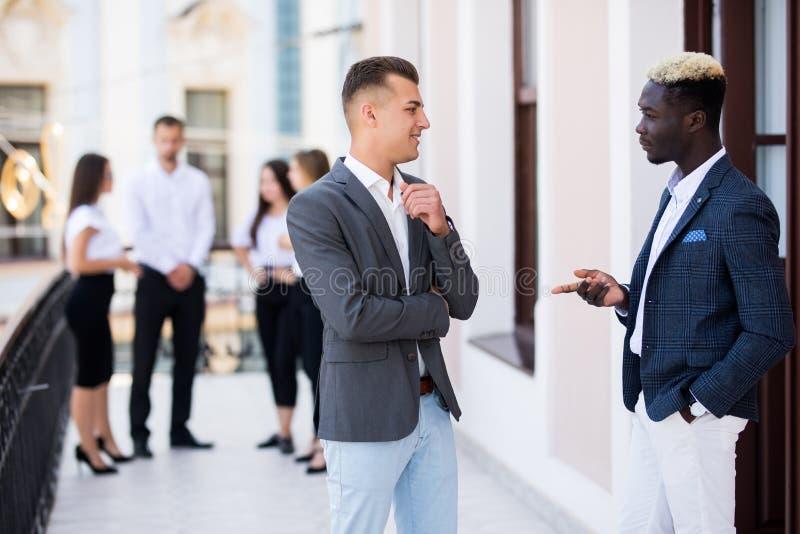看起来两个年轻的同事谈论在前面他们的企业队 免版税图库摄影