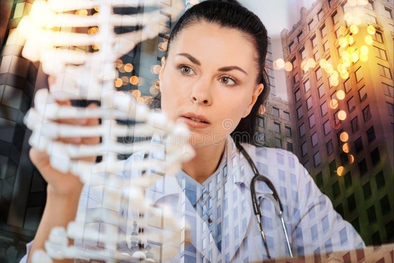 看起来严肃的医护人员殷勤,当学习脱氧核糖核酸时 库存照片