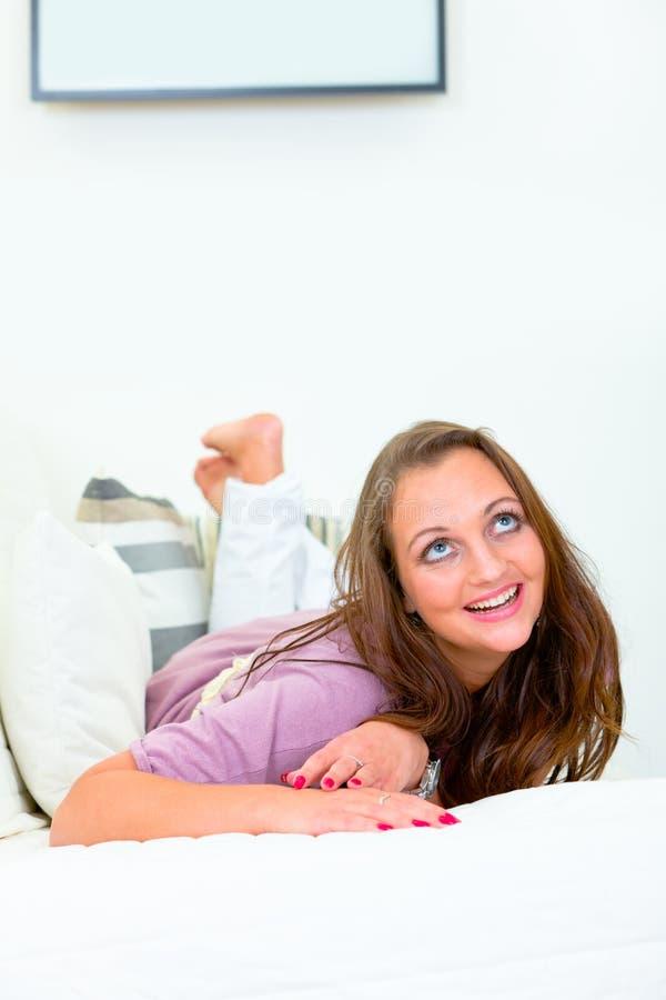 看起来位于的微笑妇女的长沙发 图库摄影