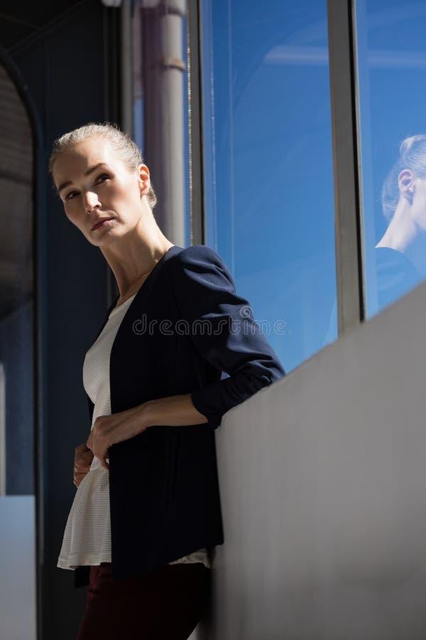 看起来体贴的女实业家去,当坚持windoew在办公室时 免版税图库摄影