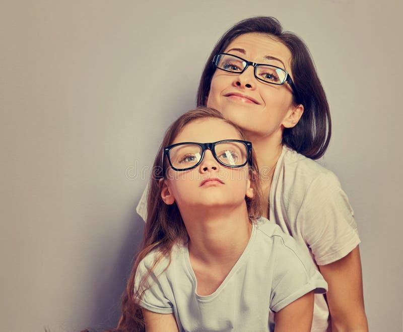 看起来做鬼脸的正面微笑的偶然的母亲与她不快乐的被触犯的想法的孩子女孩坐紫罗兰色墙壁背景 免版税图库摄影