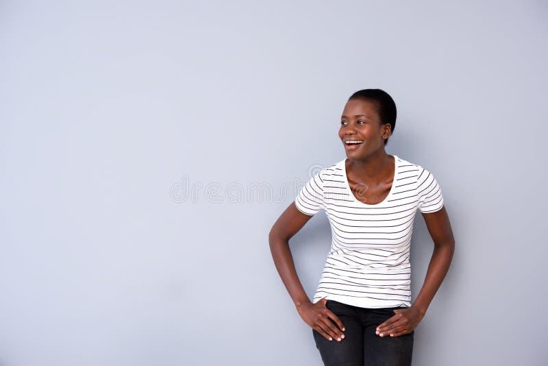 看起来去和微笑由灰色背景的时髦的年轻非洲妇女 免版税库存图片