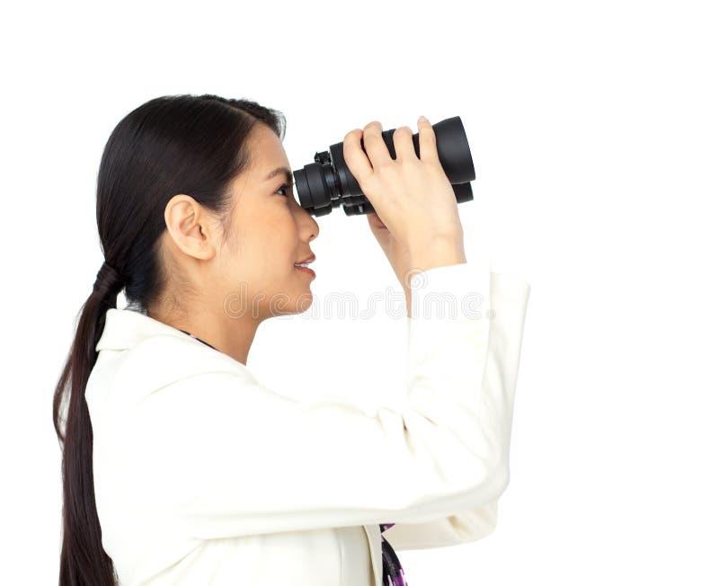 看起来双筒望远镜的女实业家幻想 图库摄影
