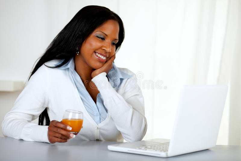 看起来可爱的微笑的学员的女孩膝上型计算机 免版税图库摄影