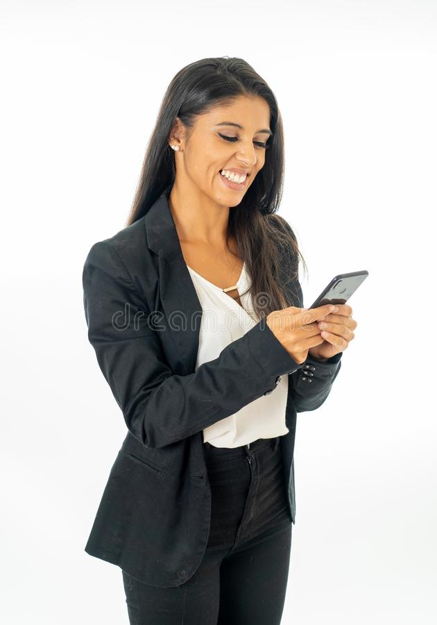 看起来可爱的拉丁公司拉丁的妇女全长画象愉快和确信使用在创造性的成功的智能手机 免版税库存图片